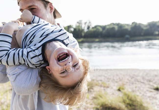 Cheerful father and son having fun at riverside — стокове фото