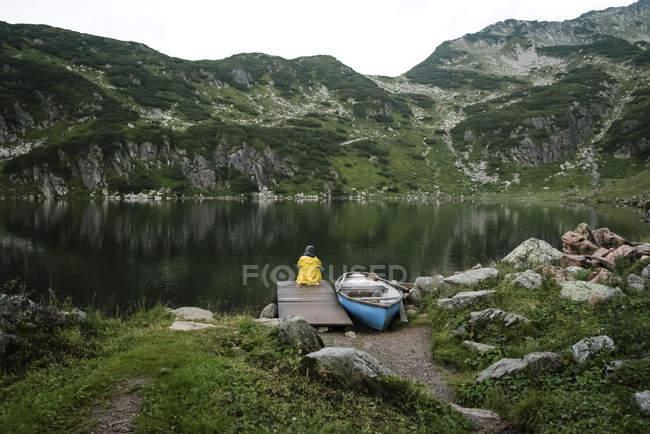 Австрія, Тіроль, Фібербрунн, Вайлдселодер, жінка, що сидить на березі озера Вайлдзее біля човна. — стокове фото
