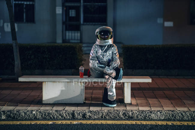 Spaceman sitting on bench at bus stop at night with soft drink — Stock Photo