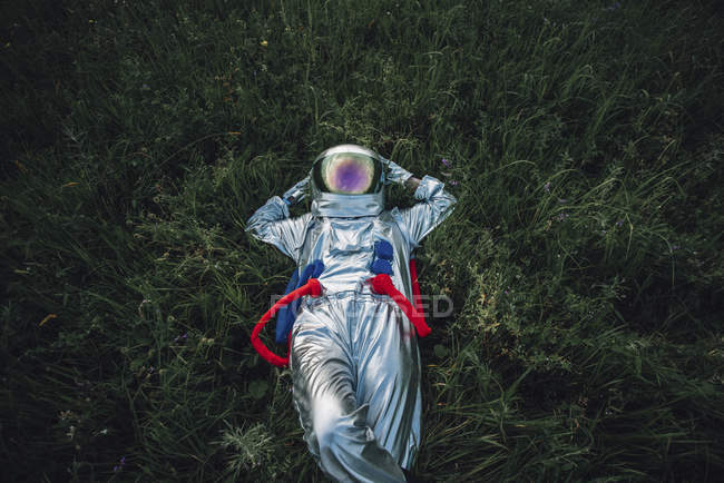 Spaceman relaxing in green meadow under cloudy sky — Stock Photo