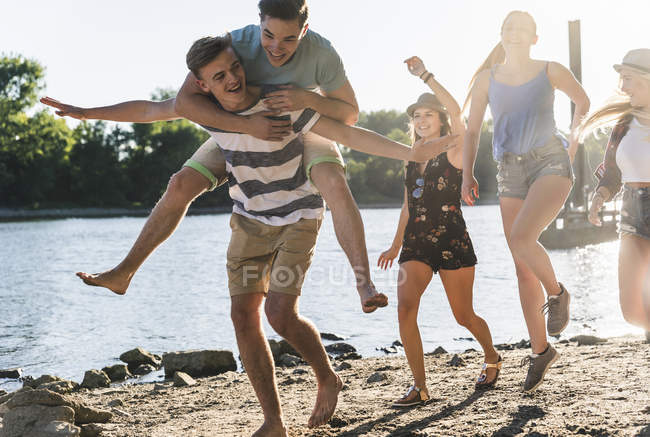 Gruppe fröhlicher Freunde amüsiert sich am Flussufer — Stockfoto