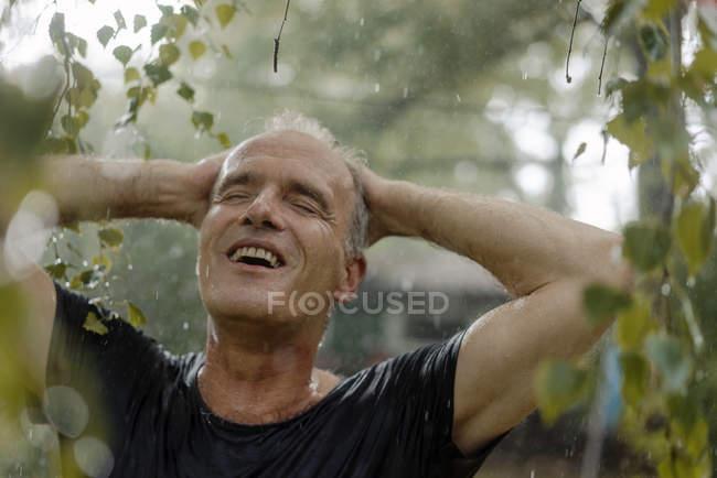 Усміхнена зріла людина, що користується літнім дощем в саду — стокове фото