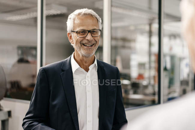 Portrait of successful entrepreneur smiling in company — Stock Photo