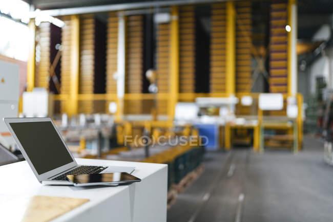 Laptop and digital tablet in logistics center — Photo de stock