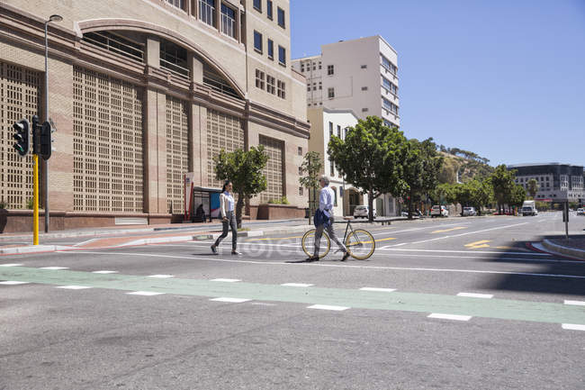 Два человека пересекают улицу в городе — стоковое фото