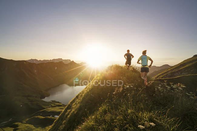 Німеччина, Альгеу Альпи, чоловік і жінка біжать гірською стежкою. — стокове фото