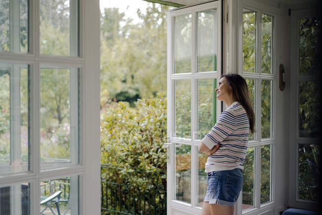 Mulher madura olhando para fora da porta do terraço em casa — Fotografia de Stock