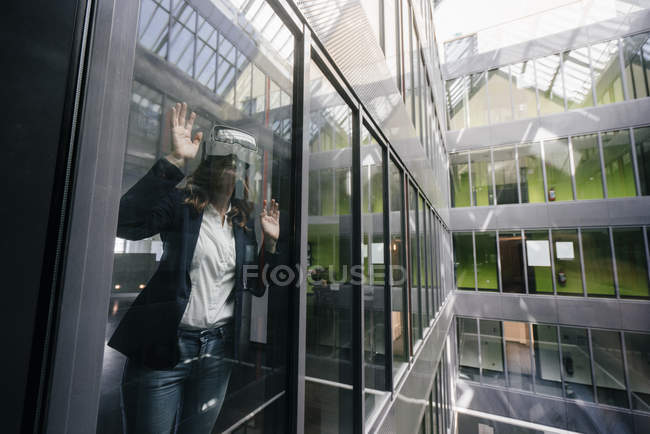 Businesswoman wearing VR goggles, standing at window — Stock Photo