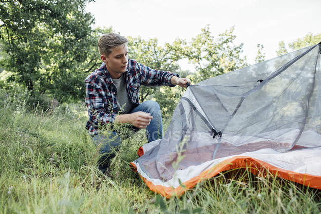 Young man camping in nature, setting up tent — стокове фото