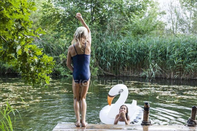 Two girls at a pond with inflatable pool toy in swan shape — Stock Photo