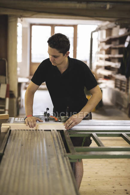 Carpenter sawing piece of wood in workshop — Stockfoto