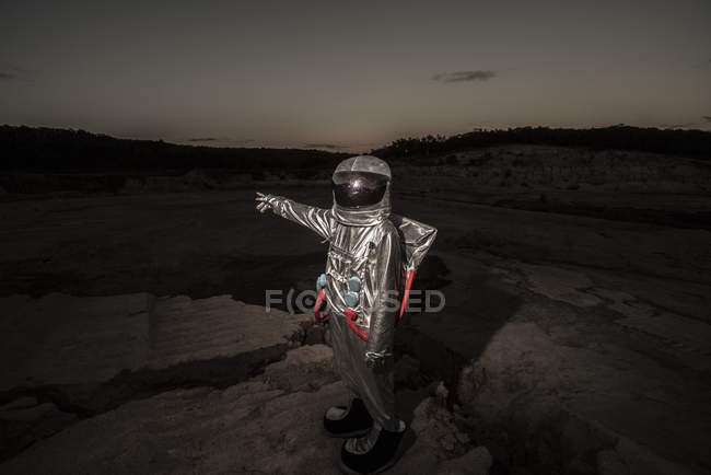 Spaceman pointing at distance at night on a nameless planet — Stock Photo