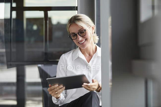 Спокойная деловая женщина сидит на земле в офисе, используя цифровой планшет — стоковое фото
