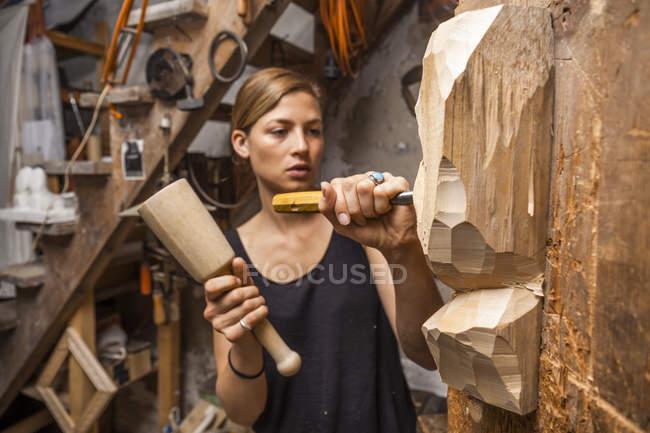 Sculptress carving wooden figure — Stock Photo