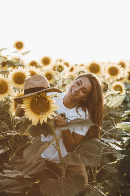 Портрет молодої жінки, яка сміється з солом'яним капелюхом, що стоїть в області соняшників — стокове фото