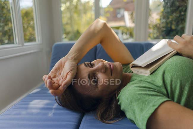 Улыбающаяся зрелая женщина лежит дома на диване с книгой — стоковое фото