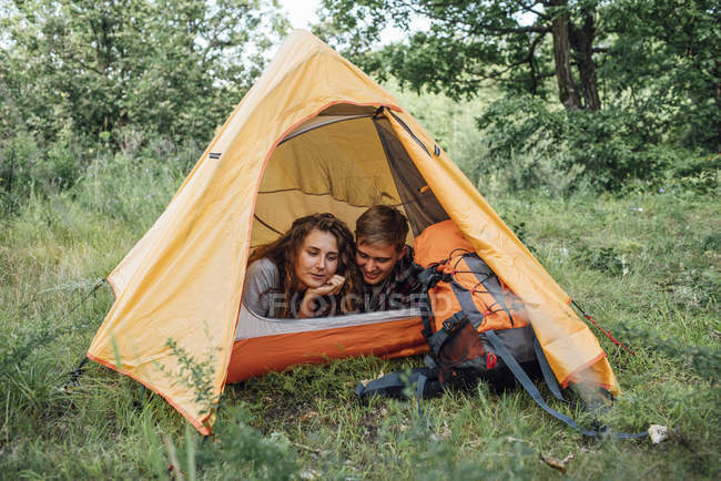 Young couple camping in nature, lying in tent — стокове фото