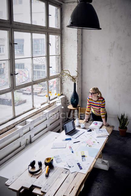 Женщина, стоящая за столом в лофте и смотрящая в окно — стоковое фото