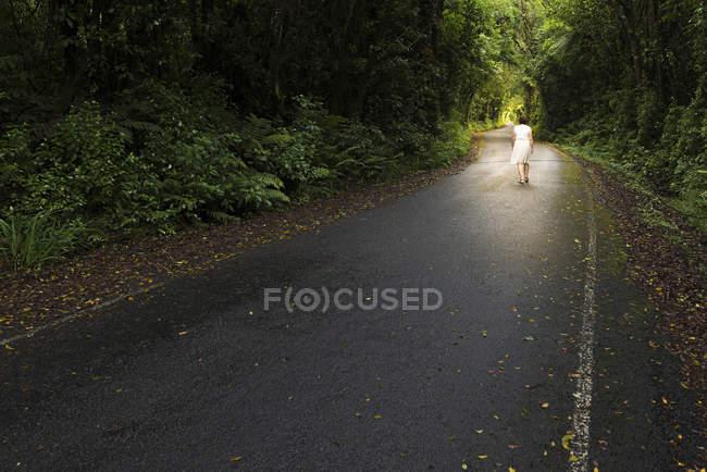 Nueva Zelanda, Isla Norte, Parque Nacional Egmont, Mujer caminando por carretera - foto de stock