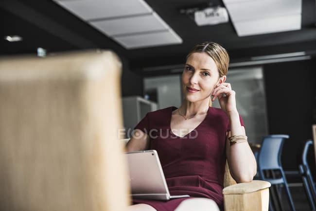 Уверенная деловая женщина в офисе в бордовом платье с помощью ноутбука и глядя в камеру — стоковое фото