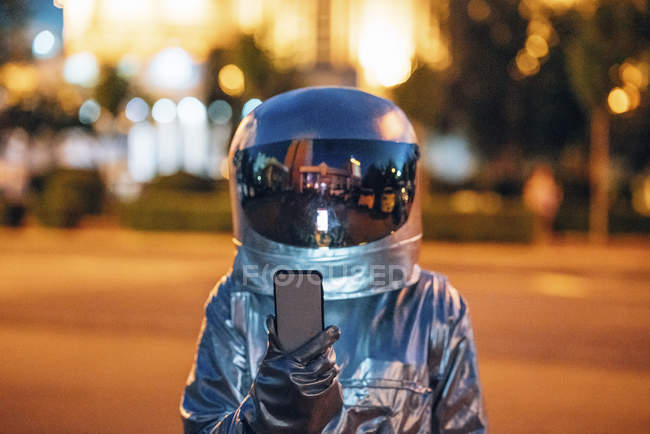 Spaceman on a street in city at night holding smartphone — Stock Photo