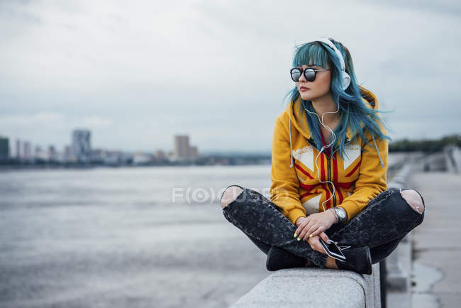 Young woman with dyed blue hair sitting on wall listening music with headphones and smartphone — Stock Photo