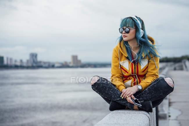 Junge Frau mit gefärbten blauen Haaren sitzt an der Wand und hört Musik mit Kopfhörer und Smartphone — Stockfoto