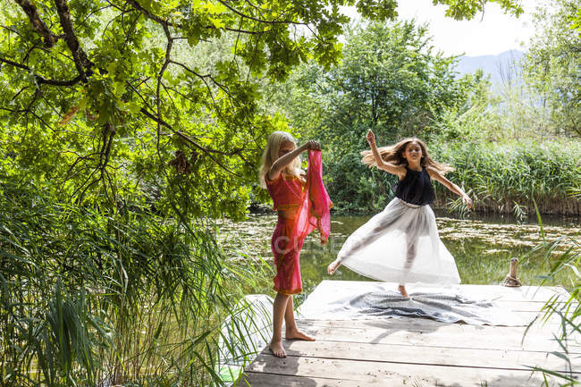 Two girls on jetty at a pond in fancy dresses — Stock Photo