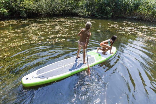 Zwei Mädchen in einem Teich auf Sup Board — Stockfoto