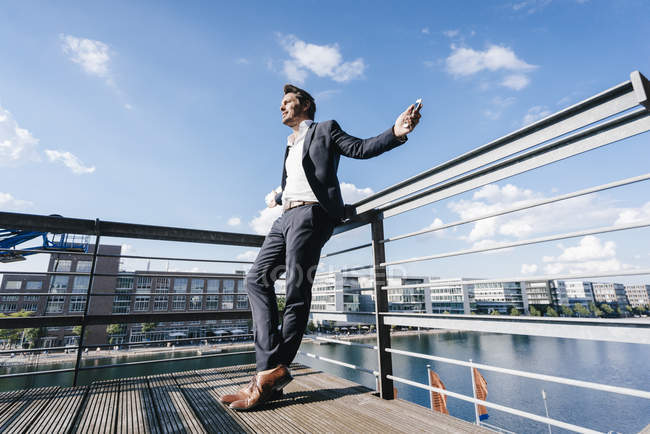 Happy businessman standing on balcony with arms out — Stock Photo