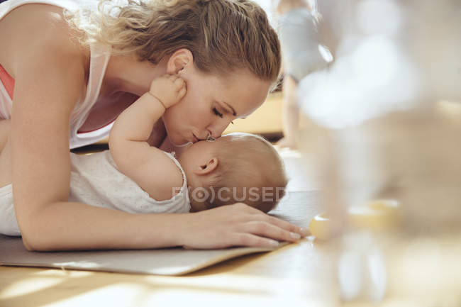 Mother kissing her baby while working out on a yoga mat — Stock Photo