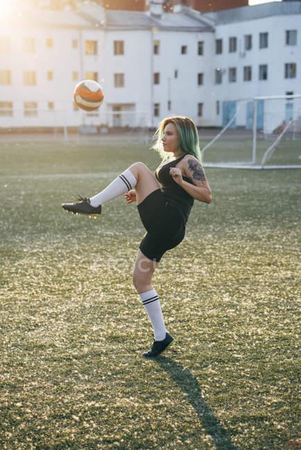 Junge Frau spielt Fußball auf Fußballplatz Balancen Balancen — Stockfoto