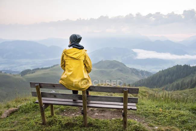 Австрія, Тіроль, Фібербрунн, Вайлдселодер, жінка сидить на лаві з видом на гори. — стокове фото