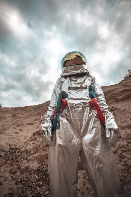 Spaceman exploring nameless planet while standing in desert — Stock Photo