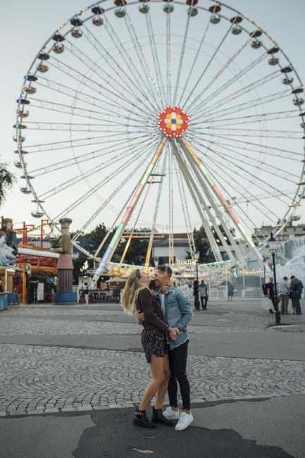 Jovem casal apaixonado, beijando e abraçando em uma feira — Fotografia de Stock