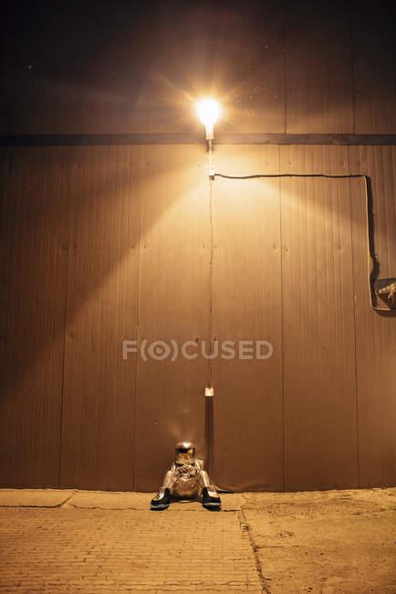 Spaceman sitting under lamp at wall at night — Stock Photo