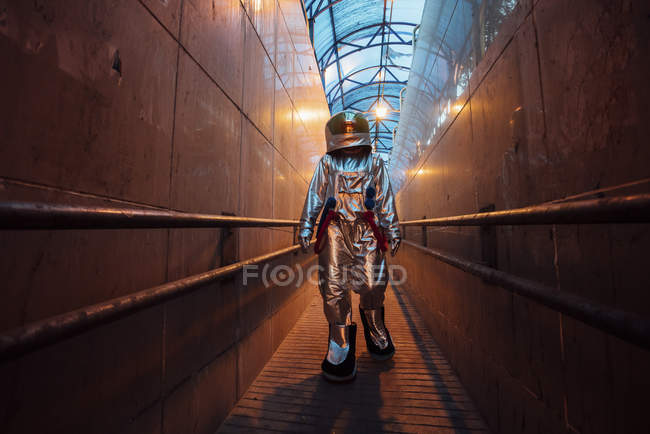 Spaceman in city at night walking in narrow passageway — Stock Photo