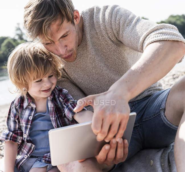 Père et fils jouant sur tablette numérique au bord de la rivière — Photo de stock