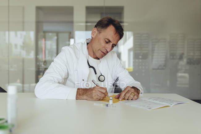 Médico sentado na prática, preenchendo cartão de imunização — Fotografia de Stock