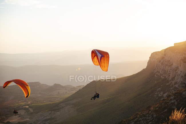Spagna, Silhouette dei parapendio che svettano in alto sopra le montagne al tramonto — Foto stock