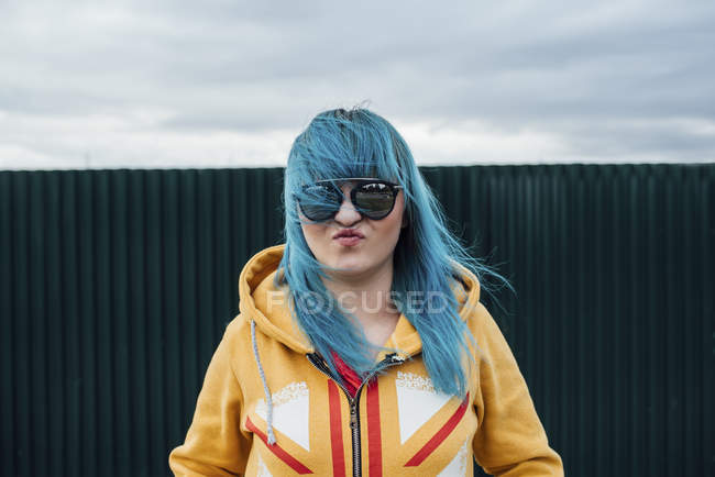 Portrait of young woman with dyed blue hair wearing sunglasses and hooded jacket — стоковое фото