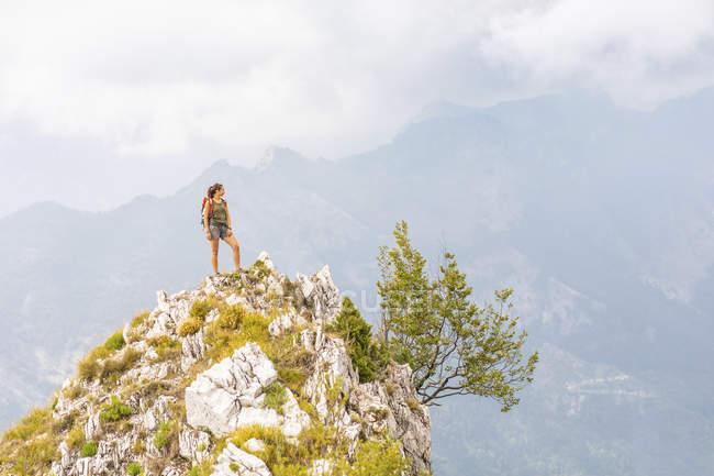 Itália, Massa, jovem mulher em pé no topo de um pico nas montanhas Alpi Apuane — Fotografia de Stock