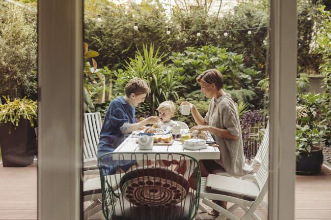 Две счастливые матери за завтраком на свежем воздухе со своим ребенком — стоковое фото