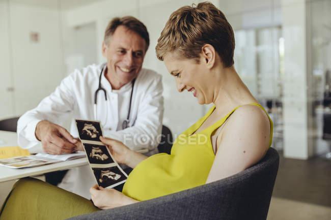 Беременная обсуждает со своим врачом ультразвуковые шрамы — стоковое фото