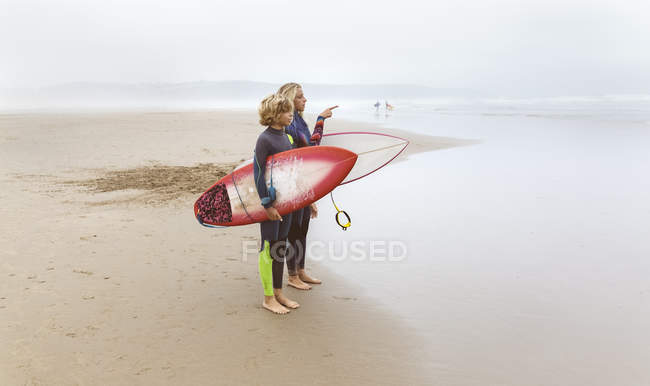 Spain, Aviles, two young surfers holding surfboards on beach — Stock Photo
