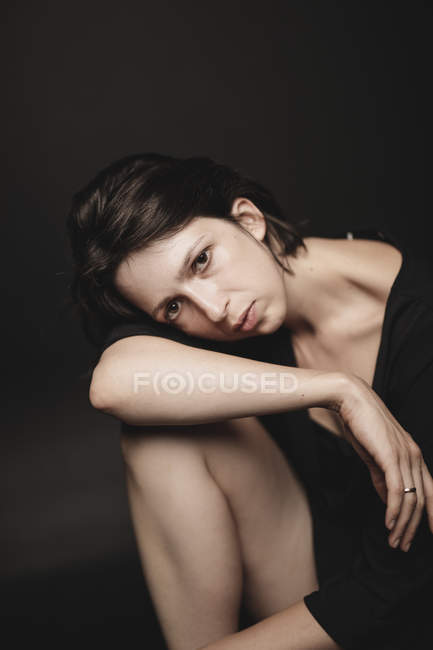Portrait of sad woman sitting in front of black background — Stock Photo