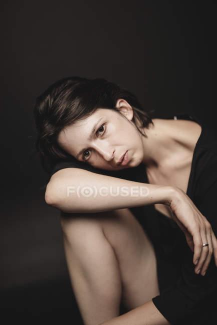 Портрет грустной женщины, сидящей перед черным фоном — стоковое фото