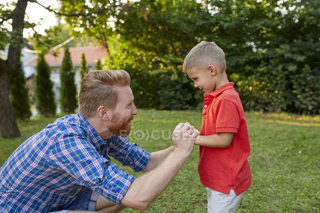 Happy father with his son in garden — Stock Photo
