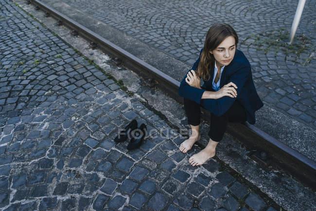 Empresária descalça sentada no trilho na rua — Fotografia de Stock