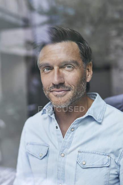 Retrato de homem sorridente atrás do vidro da janela — Fotografia de Stock